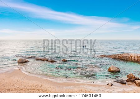sea in the morning sunrise with bright blue sky and fisherman in small fishing boat rayong province thailand