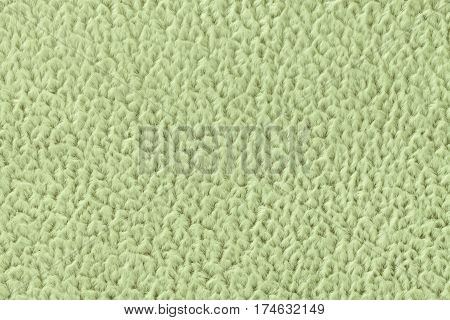 Light green fluffy background of soft fleecy cloth. Texture of textile closeup.