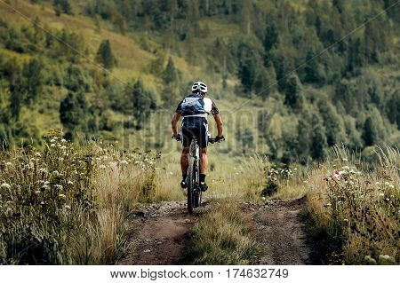athlete cyclist mountainbiker with backpack downhill on trail
