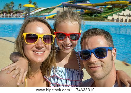 Happy family taking selfie on vacations in aqua park.