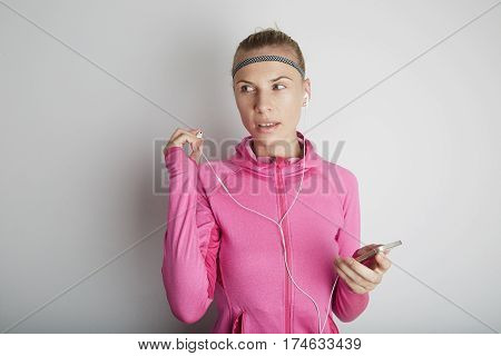 Portrait of fitness young woman wearing pink sports wear. Fresh healthy stylish sport girl listening energetic music.