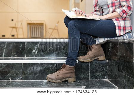 Body of female Student in heavy leather Boots jeans Pants and casual Shirt holding notepad and telephone sitting on Stairs in University chat room area