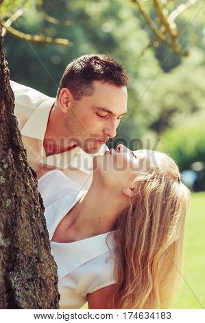 Love romantic walks concept. Man and blonde woman having romantic date in park happy being together kissing behind tree