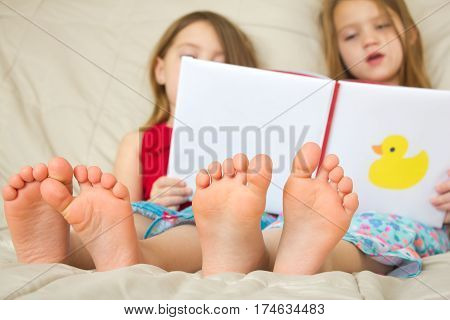 Two children reading a book in bed