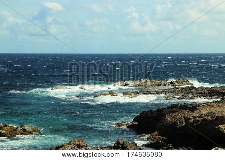 water crashing into a rocky shore on a clear day