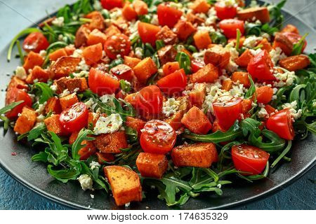 Sweet potato, carrots, cherry tomatoes and wild rocket salad with feta cheese served in black plate.