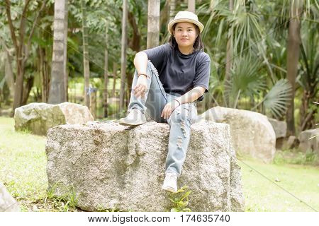 Young Woman Sitting On A Big Rock