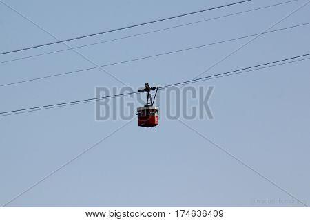 Fotografía de teleférico rojo sobre fondo de cielo azul