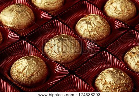 Chocolate candies close up in gold wrapper