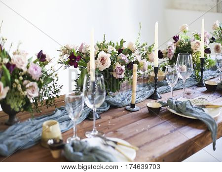 Bouquets of pink flowers on a table set for dinner with candles close up