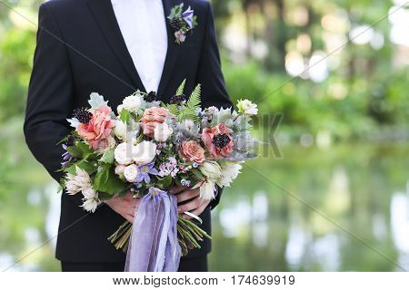 Groom holding beautiful bouquet in his hands closeup
