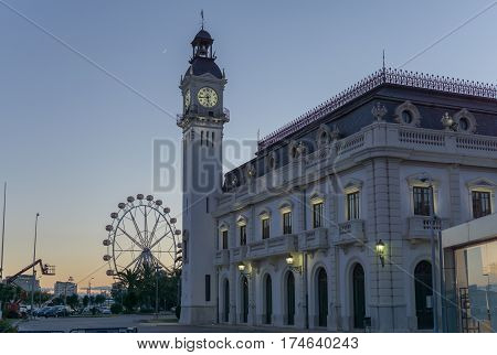 Night sunset view Port Authority buildings with clock tower in Valencia harbor, Spain. Background ferris wheel and moon