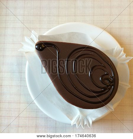 Chocolate Cake With Ganache Glaze decorate with chocolate hot fudge sauce with blur background tablecloth tea time closed-up top view