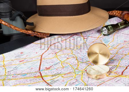 Tourism concept. Compass on city map with flashlight fedora hat bullwhip and binocular in the background. Selective focus.