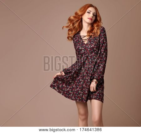 Fashion Boho woman. Stylish Curly Volume Hairstyle, fashion Makeup. Glamour Redhead Beauty Lady, Sexy fashion pose. Trendy Summer Dress. Playful Romantic Girl, Floral Outfit, summer boho Accessories