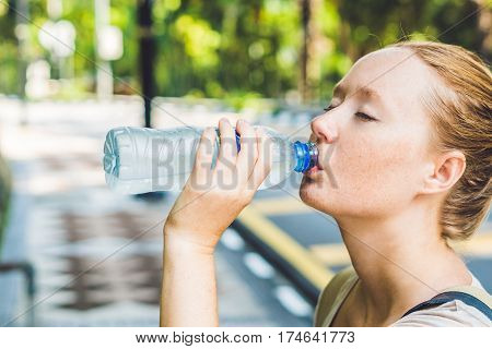 Young Woman In Hot Weather Drinks Water From A Bottle