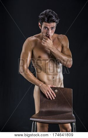 Portrait of naked handsome young man with languishing look covering crotch behind chair