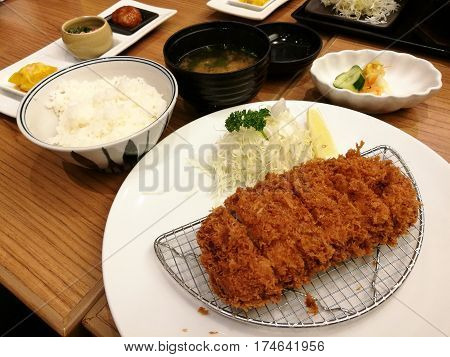 Deep-fried pork slice cabbage set served with rice and soup lemon and mayonnaise or tartar sauce in restaurant Pork cutlet set Japanese pork Tonkatsu focus-on-foreground with blur background