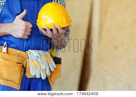 Worker in hardhat and tool belt at construction site