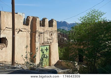Derelict old earthen house  in ruin under a clear sky