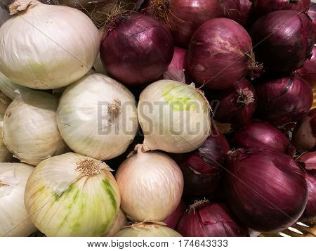 Fresh organic white onion bulbs and red shallot among many onion and shallot background in the basket in supermarket. Heap of onion root. Close-up red onion shallot texture