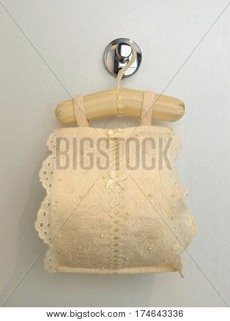 Roll tissue cloth lace fabric cover with toilet paper roll for sanitary inside hanging on white background bathroom closed up