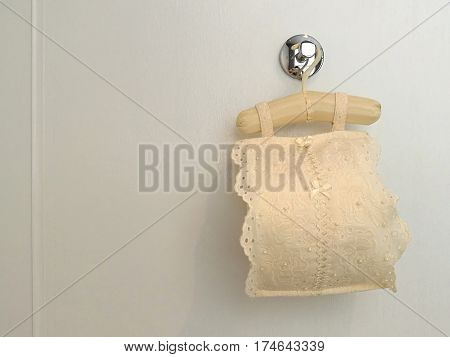 Roll tissue cloth lace fabric cover with toilet paper roll for sanitary inside hanging on white background bathroom closed up with space