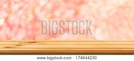 Wooden board empty table pink cherry blossom flower. Perspective brown wood table blur trees forest background - can be used mock up for display montage your products. spring season. panoramic banner.