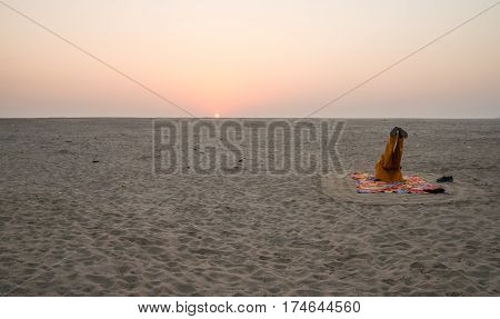 Person doing yoga in the morning time on riverbank of Ganges, India