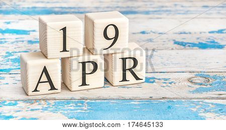 April 19th. Wooden cubes with date of 19 April on old blue wooden background.