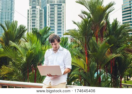 Man Businessman Or Student In Casual Dress Using Laptop In A Tropical Park On The Background Of Skys