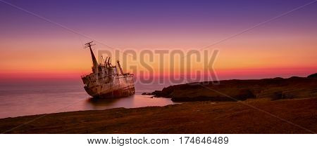 Seascape: famouse boat shipwrecked near the rocky shore at the sunset. Mediterranean near Paphos. Cyprus.