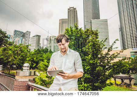 Man Businessman Or Student In Casual Dress Using Tablet A Tropical Park On The Background Of Skyscra