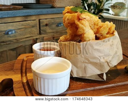 Stylist food deep fried calamari on paper bag with chilli sauce and mayonnaise or tartar sauce serve on the wooden tray with blur restaurant background side view