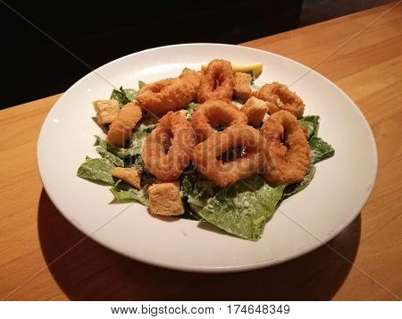 Stylist food deep fried calamari on white plate serve with Caesar Salad on the wooden table with blur restaurant table background top view