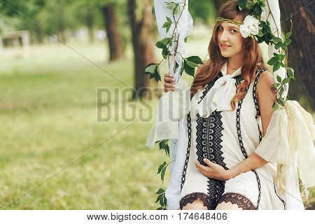 Gorgeous Pregnant Woman In Stylish Retro Black & White Dress And Roses Wreath Posing On Fairytale Sw
