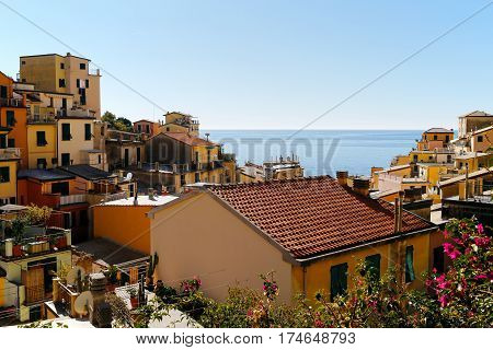One of Cinque Terre villages, Riomaggiore, with blue sea and sky in the background. Cinque Terre was included as a UNESCO World Heritage Site in 1997.