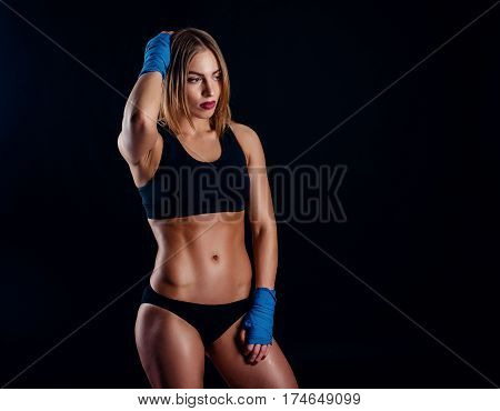 Attractive Athletic Woman With The Blue Boxing Wraps On Black Background In Studio. Tanned Sporty Gi