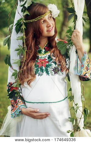 Beautiful Pregnant Woman In Traditional White Dress On Swing In Park Closeup