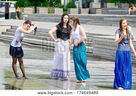 MOSCOW, RUSSIA - May 30, 2016: Unknown girls bathing city fountain. Hot summer heat. Girls in wet skirt and blouse. Wet long hair. Bright emotions face. Icy freshness, happiness.Street stories,romance