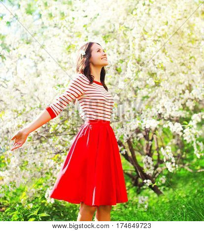 Happy Pretty Woman Enjoying Smell Flowers Over Spring Garden Background