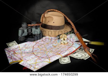 Tourism and adventure concept. Compass on city map with flashlight fedora hat bullwhip binocular knife and dollar bills on dark background.