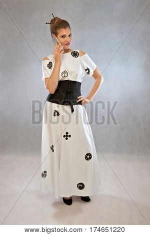 Woman with mobile phone in a dress inspired by the Japanese kimono