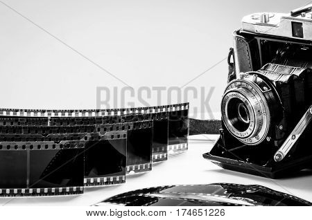 black and white photo of an old analogue camera displayed with negatives