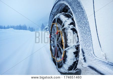 Car driving with snow chains for tire on the snow-covered road