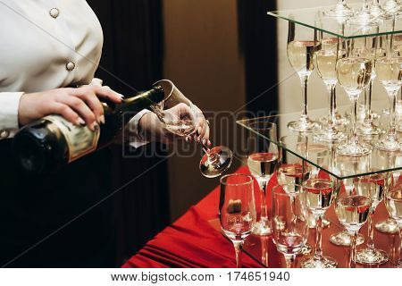 Elegant Waiter Pouring Sparkly Champagne Into Group Of Glasses At Luxury Business Corporate Retreat