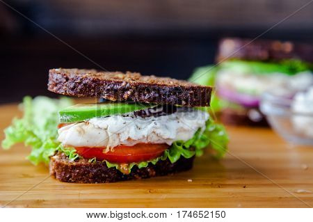 Fresh homemade sandwich with cereals dark rye grain bread, salad lettuce, avocado, tomato, grilled chicken breast, curd cheese and greengrocery on on wooden table. Healthy lifestyle breakfast.