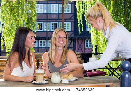 Female waiter serving coffee to young pretty women customers sitting at street cafe table and cheerfully smiling with European city architecture and green trees in background