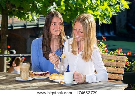 Two Pretty Woman Eating In Outdoor Cafe
