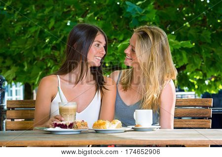 Two Young Women Sitting Close In Outdoors Cafe
